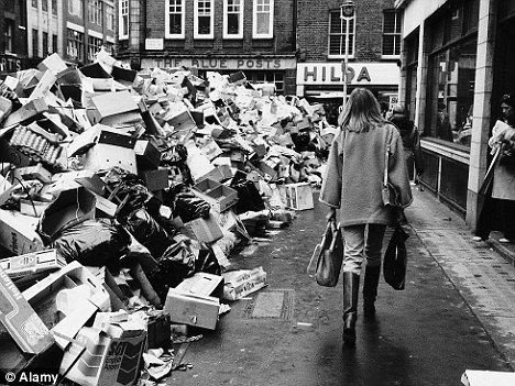 Black and white photo of woman walking past piles of rubbish during the winter of discontent