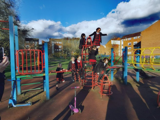 A group of school children wearing uniforms pose for a photograph on a climbing frame in a sunny city park